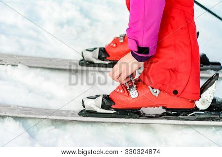 poster of Skier In Red Ski Suit And Red Ski Boots And White Skis, Closeup.