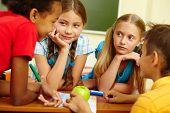 Portrait of friendly schoolchildren chatting in classroom