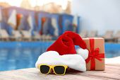 Authentic Santa Claus Hat, Gift Box And Sunglasses Near Pool At Resort poster