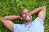 African American Man Lying In Grass Listening To Music