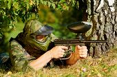 paintball sport player in protective uniform and mask aiming and shooting with marker paintballing gun outdoors