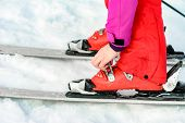 Skier In Red Ski Suit And Red Ski Boots And White Skis, Closeup. poster