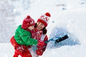 Mother And Child Brushing And Shoveling Snow Off Car After Storm. Parent And Kid With Winter Brush A poster