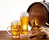 Beer barrel with beer glasses on a wooden table. Isolated on a white background.