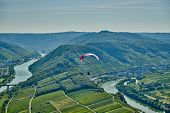 Paraglider over Moselle River bend near Bremm town, Germany. Hills with vineyards, river loop and ro poster