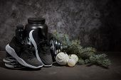 Sports nutrition (supplements), dumbbell, sneakers, branch of fir and Christmas ornaments on dark gr poster
