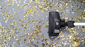 Vacuum Cleaner Cleans Up Bright Confetti. The Party Is Over. House Cleaning. Close-up. Top View. poster