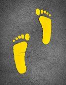 Yellow Footprint Painted On Asphalt Road. Walkway Lane Traffic Sign. Foot Mark On Street Texture Bac poster