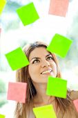Multitask woman with post-its all around and smiling