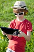 Boy Playing With Enthusiasm In The Tablet Pc