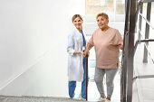Nurse Assisting Elderly Woman On Stairs Indoors poster