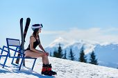 Skier Girl In Black Swimsuit And Helmet, Sitting At A Bench Near Skis And Enjoing Wonderfull View At poster