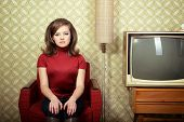 art portrait of young woman sitting on chair and looking at camera in room with vintage wallpaper an
