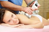 young beautiful woman getting massage therapy on back in beauty salon