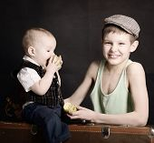 vintage art portrait of little boy with his baby brother leaning on old suitcase and eating apples,