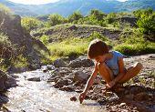 juego de niño con que fluye agua en montaña, naturaleza de verano al aire libre