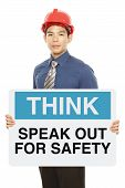 picture of osha  - A man wearing a hardhat and holding a signboard with a safety reminder - JPG
