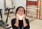 Woman with cervical collar in rehabilitation room