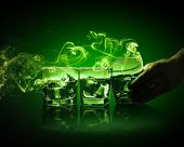 Hand holding one of three glasses of green absinth with fume going out