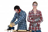 a man using a circular saw and a woman