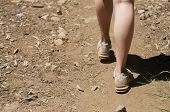 Empty space left close up of woman's feet hiking in dirt