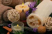 Spa concept with aromatic candles, lavender, massage oil, cotton towels and loofah
