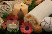 Spa concept with aromatic candles, herbs, beautiful daisies, massage oil and loofah