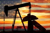 picture of early morning  - Landscape image of a oil well pumpjack wiith an early morning golden sunrise and American USA red White and Blue Flag background - JPG