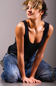sexy fashionable knelt down woman wearing black tank top and jeans