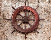 picture of ship steering wheel  - Old wooden ship steering wheel on stone wall - JPG