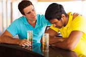 young man sitting at bar and comforting his sad friend