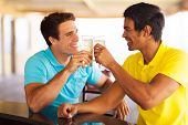 cheerful friends having beer at the pub, clinking glasses