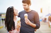 romantic couple with ice cream at amusement park