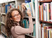 stock photo of time study  - Young female student is looking for a book in the library - JPG