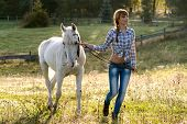 Beautiful young woman with a white horse in the country