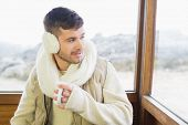 Thoughtful young man wearing earmuff with coffee cup against cabin window
