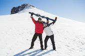 Full length of a cheerful couple with ski board standing on snow covered landscape