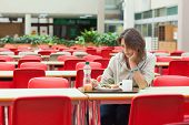 Alone and sad female student sitting in the cafeteria with food tray