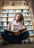 Full length of a female student sitting against bookshelf and reading a book on the library floor