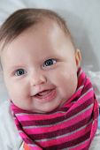 stock photo of cherub  - Portrait of a beautiful smiling newborn baby girl with a happy chubby cherubic face and look of contented innocence - JPG