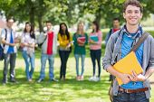 Portrait of college boy holding books with blurred students standing in the park
