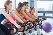 Side view of four people working out on exercise bikes