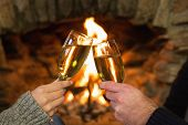 Close-up of hands toasting champagne flutes in front of lit fireplace
