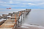 Abandoned pier. Old dilapidated pier in the Strait of Magellan. In the distance the two cargo ships