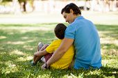 stock photo of role model  - Young father and his son relaxing and spending time together in a park - JPG