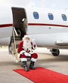 Full length portrait of Santa Claus toasting milk glass while sitting on private jet's ladder