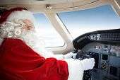 Portrait of man in Santa costume holding control wheel in cockpit of private jet
