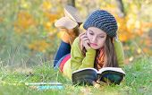 beautiful girl reading a book outdoor in autumn time