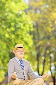 Senior gentleman meditating seated on a green grass in a park