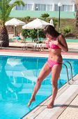 Young Woman In Swimwear Shudders At The Feet Touch Of Cold Water In The Pool